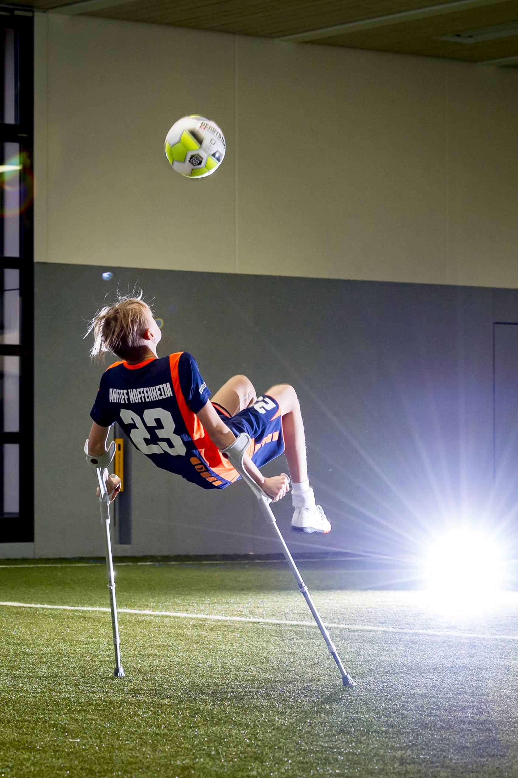 Jugendlicher einbeiniger Amputierten Fußballer auf Krücken beim Fallrückzieher in einer Kunstrasenhalle