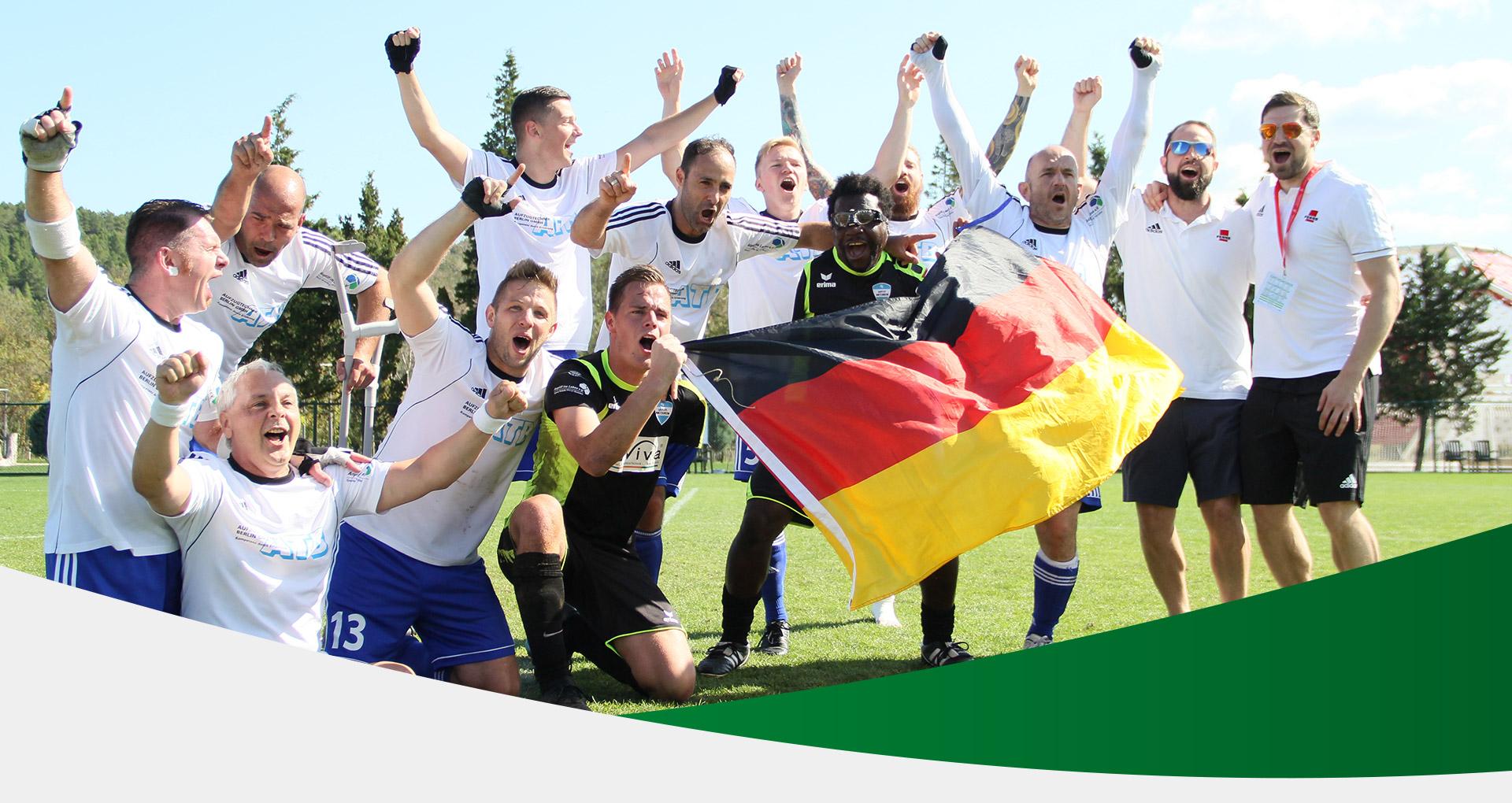 Kopfbild: jubelnde Amputierten Fußballmannschaft in einem Stadion. Die beiden Torhüter halten eine Deutschlandfahne hoch