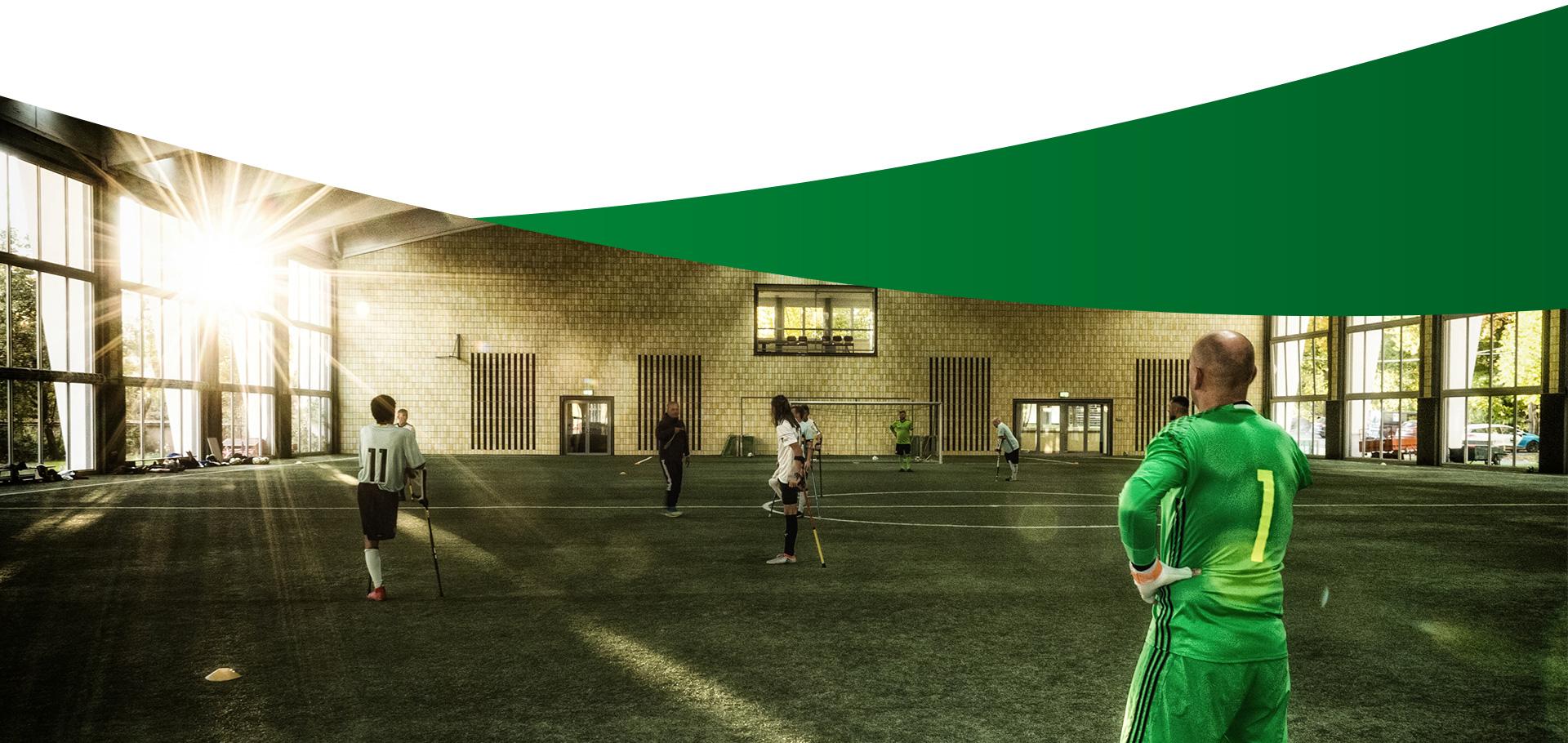 Abschlußbild Historie: Amputierten Fußballmannschaft in einer lichtdurchfluteten Kunstrasenhalle beim Training