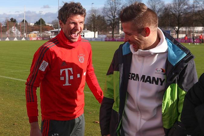 Fußball-Nationalspieler Thomas Müller und Amputierten-Fußball-Nationalspieler Christian Heintz lachend auf einem Rasenplatz
