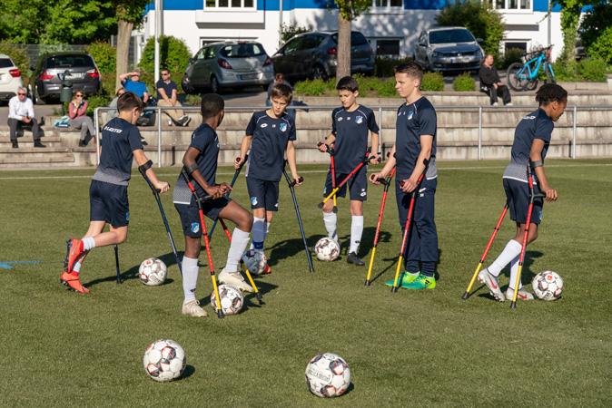 Training U13 TSG: 6 jugendliche Fußballer beim Training auf Krücken auf einem Rasenplatz