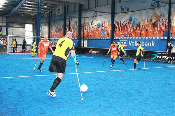 Turnier Spielwochenende Braunschweig, Amputierten Fußballspiel mit Krücken in einer Halle auf blauem Kunstrasen