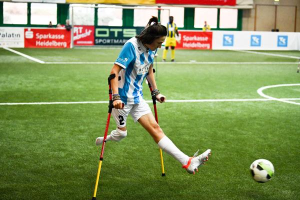 einbeiniger Amputierten Fußballer auf Krücken läuft in einer Kunstrasenhalle und kickt den Ball vor sich her