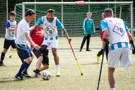 Drei Amputierten-Fußballer auf Krücken im Kampf um den Ball. Zwei weitere Spieler schauen zu.