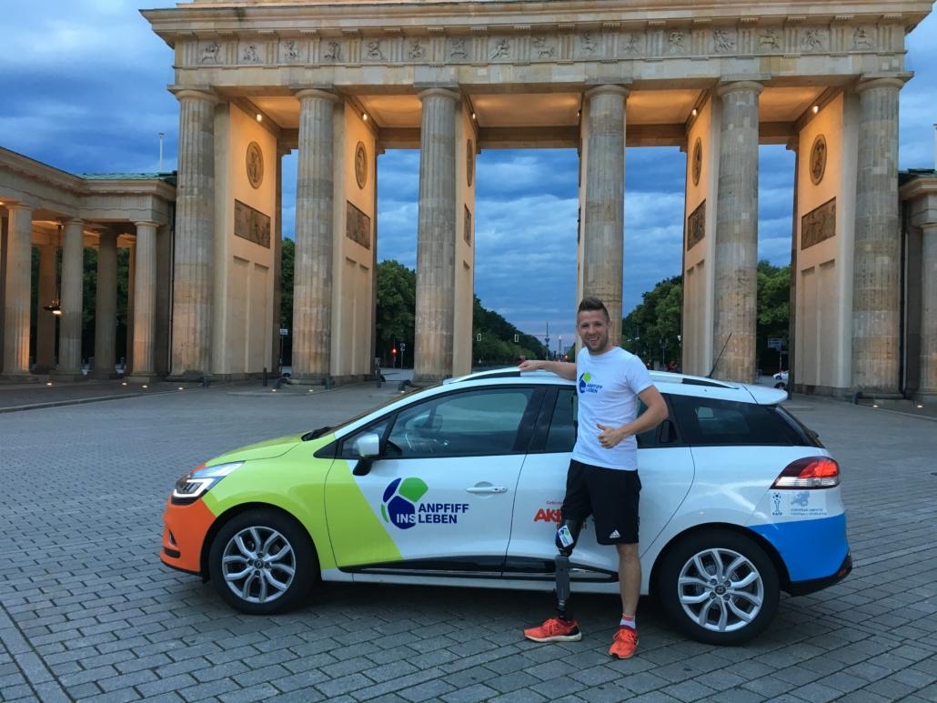 Amputierten Fußballer Christian Heintz mit seinem Auto direkt vor dem Brandenburger Tor in der Dämmerung