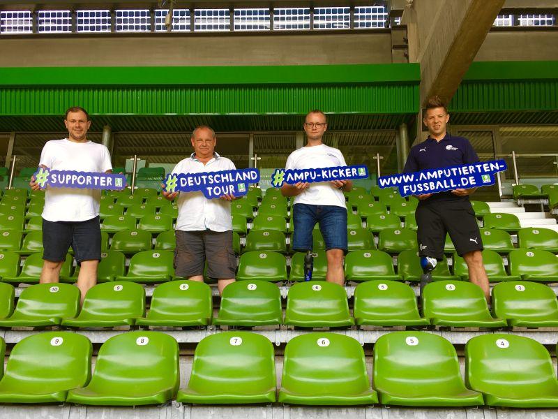 Christian Heintz steht neben Slawomir Roszczewski, Wolfgang Rasic und Christoph Schlobohm vom Fußballverband Bremen im Stadion von Werder Bremen.