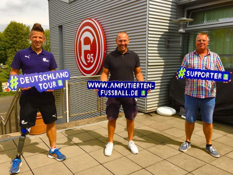 Christian Heintz steht neben Stefan Felix von Fortuna Düsseldorf und Axel Müller vom Fußballverband Niederrhein. Alle halten Werbeschilder in der Hand.