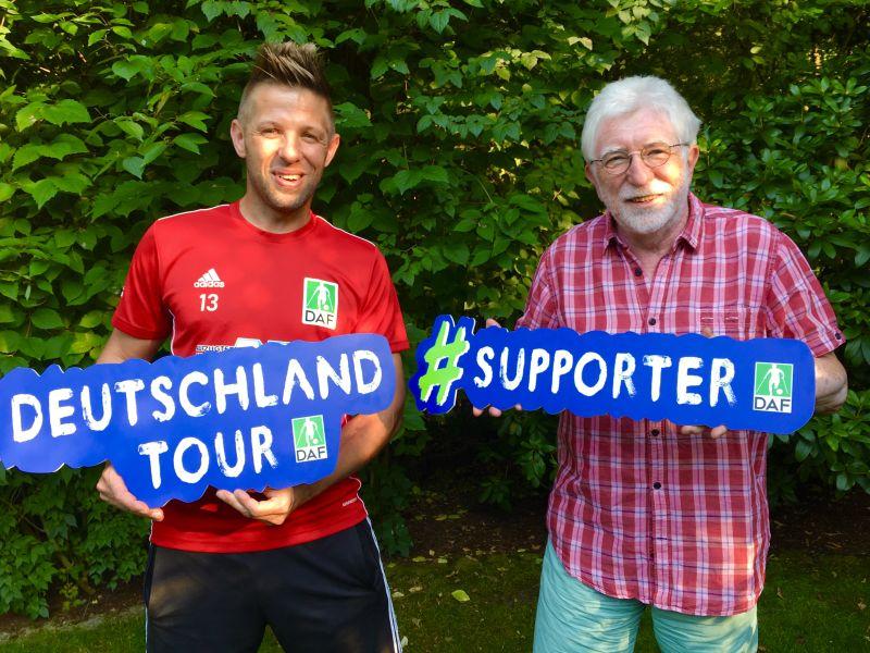 Christian Heintz und Rolf Husman stehen in einem Garten. Beide halten Werbeschilder in der Hand.