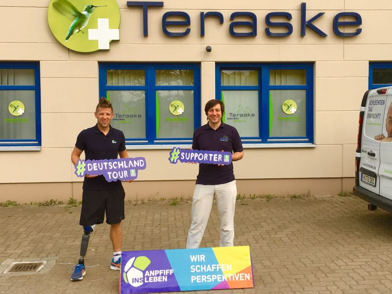 Christian Heintz und Doktor Fabian Elfeld stehen vor einem Gebäude. Beide halten Werbeschilder in der Hand. Im Hintergrund sieht man das Logo der Firma Teraske.