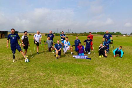 16 Amputierten-Fußballer beim Gruppenbild auf einem Rasenplatz