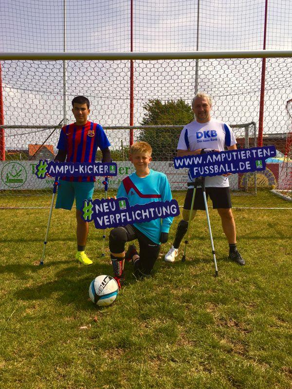Die beinamputierten Spieler Mahjed und Ronny stehen mit Werbeschildern in der Hand auf einem Fußballplatz. Der armamputierte Spieler Lucio kniet davor mit einem Werbeschild in der hand.