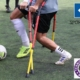 Zwei amputierte Fußballer auf Krücken im Zweikampf um den Ball auf Kunstrasen.