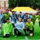 Zwei Mannschaften im Amputierten-Fußball beim gemeinsamen Gruppenfoto auf einem Kunstrasenplatz