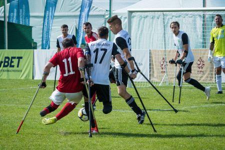 Zwei amputierte Fußballer auf Krücken im Zweikampf um den Ball auf Rasen.